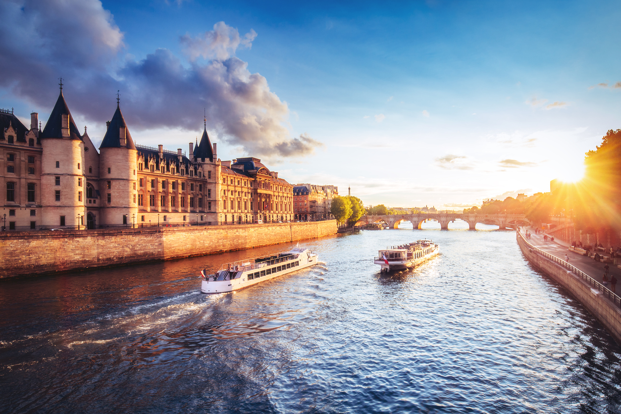 Dramatic sunset over river Seine in Paris, France, with Conciergerie and cruise boats