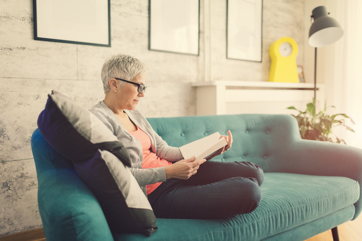 Mature woman reading book at home